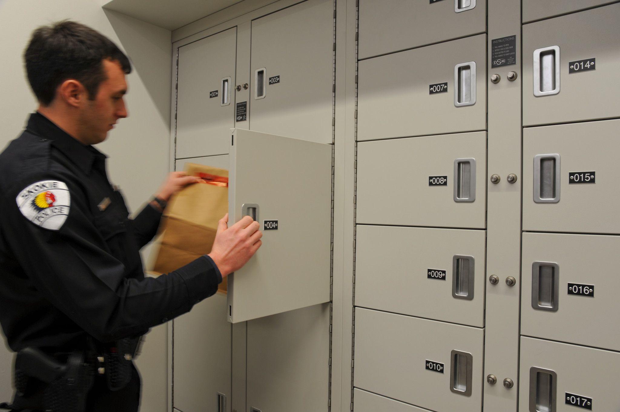Police officer depositing evidence into secure pass thru locker