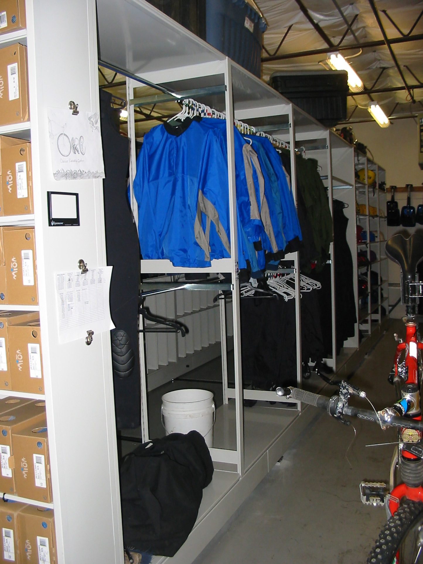 Outdoor apparel storage on hanging racks inside mobile shelving unit at Outdoor Resource Center at Brigham University