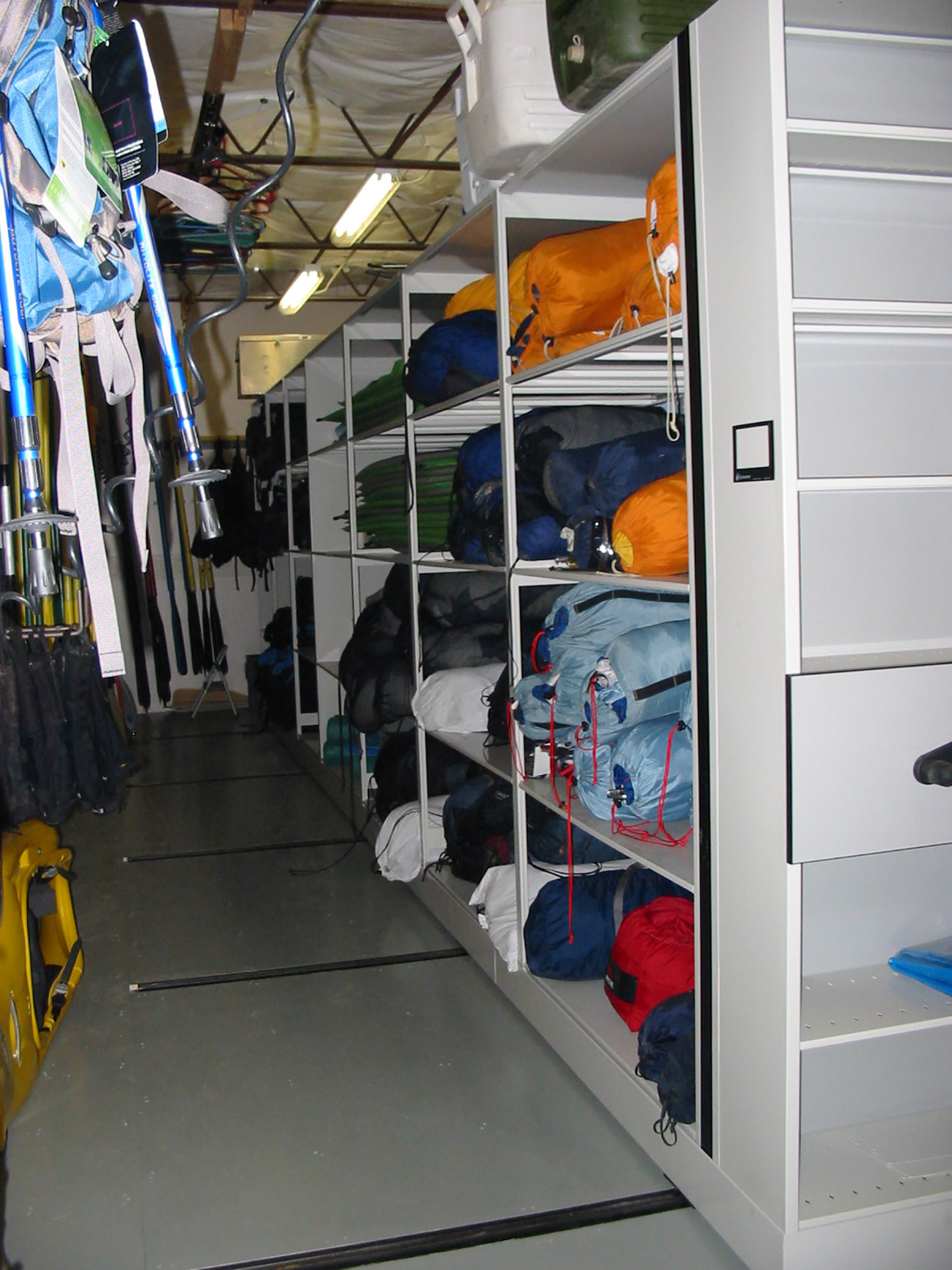 Sleeping bag storage on shelves of mechanical assist mobile storage system at Outdoor Resource center, Brigham University
