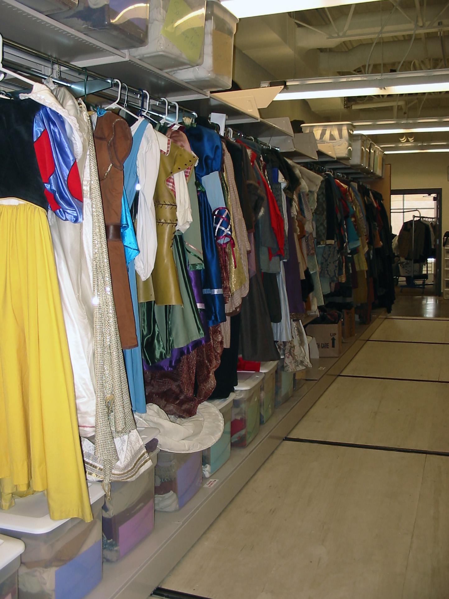 Shelving on top and bottom holds props while costumes hang from clothing rod at Brigham Young University Performing Arts Center