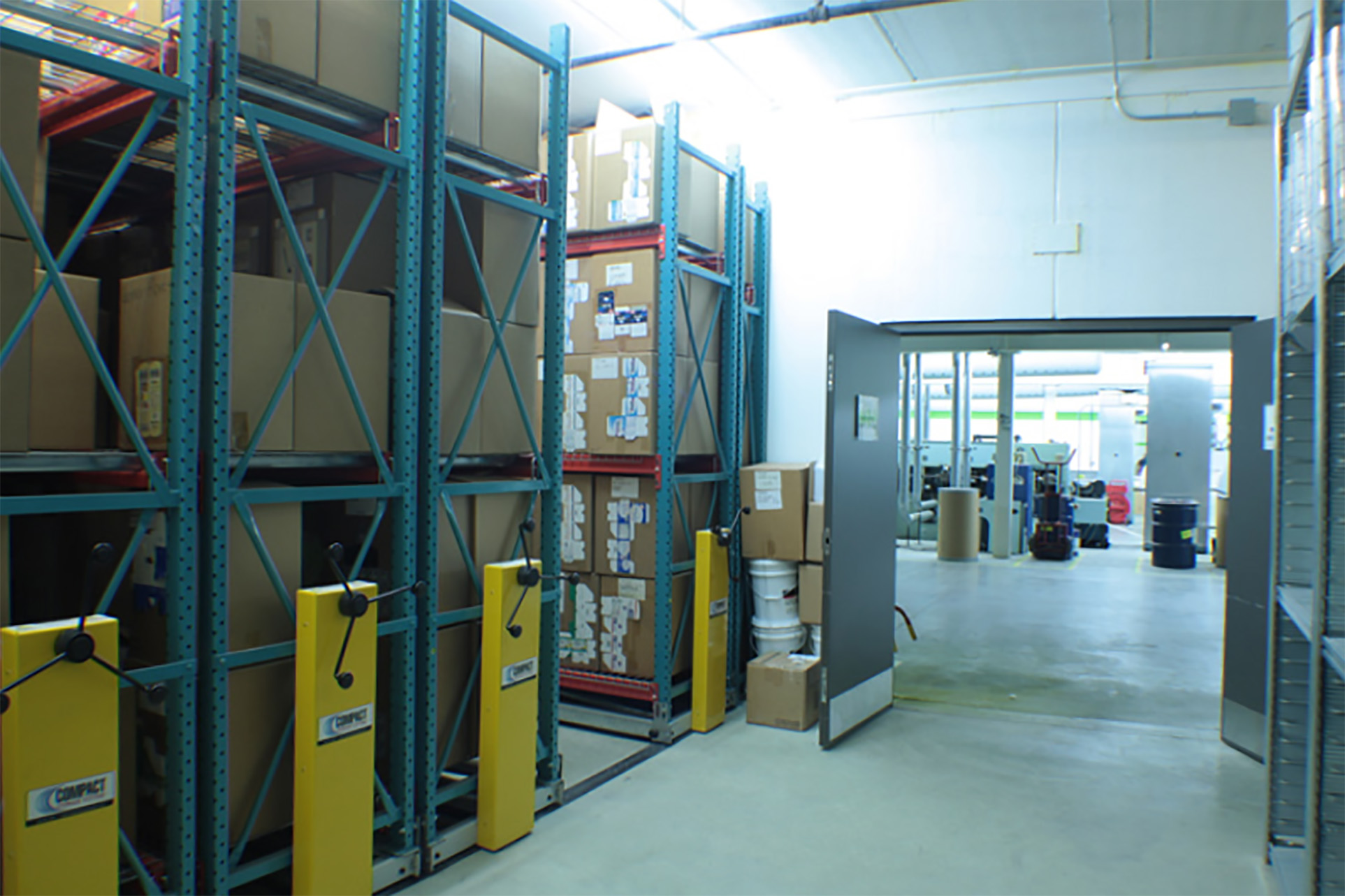 Printing supplies on mechanical assist compact warehouse racking system