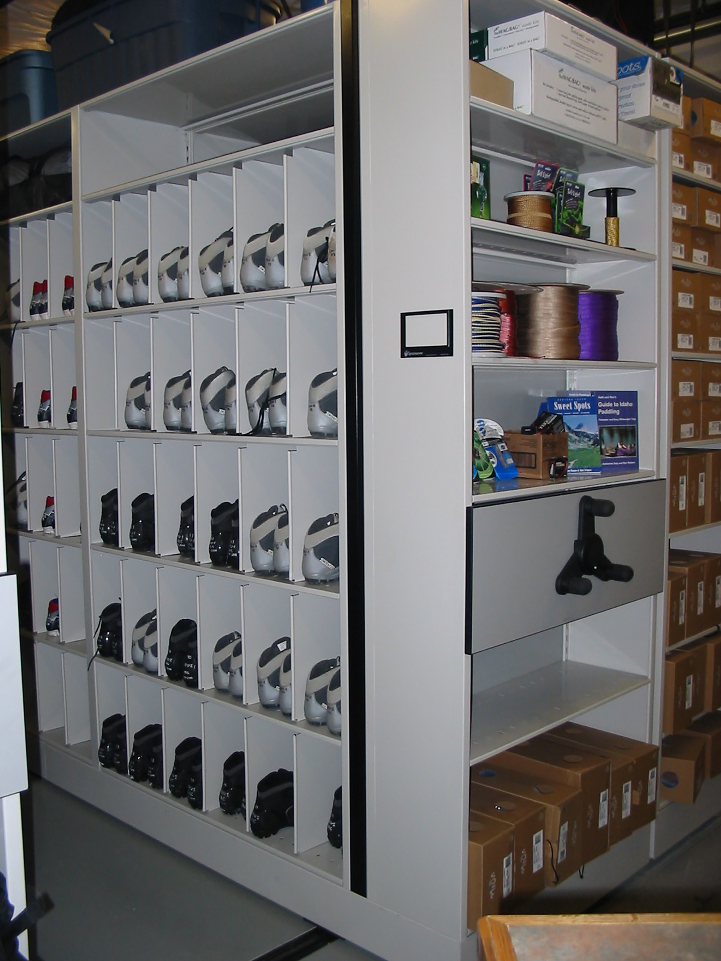 Cross country ski boots stored in bins on mechanical assist mobile shelving at Brigham Young University Outdoor Resource Center